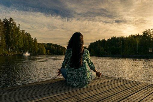 Tjej som sitter i yogaställning på en brygga, fotat bakifrån